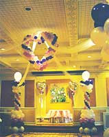 This 5 foot tall balloon heart sculpture is suspended from the ceiling as a focal decoration at a wedding reception