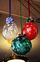 Balloonatics 24 inch diameter Christmas decoration balls are encased in clear long-lasting mylar balloons and serve as an excellent holiday party ceiling decoration
