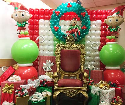 A gold adorned chair for visits from Santa framed by colorful holiday color balloons.