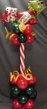 This 24' high centerpiece, combines a red and white candy cane column with an assortment of mylar gift package balloons.