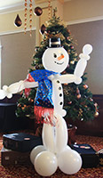 Balloonatics eight foot tall snowman figure sculpture creared from non-round white balloons with black hat to serve as a cheerful greeter to party guests