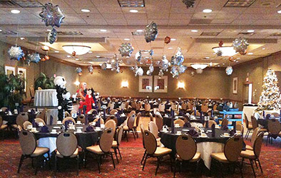 Sparkling mylar snowflake balloons placed accross the ceiling of this holiday party room to create a snowstorm illusion.