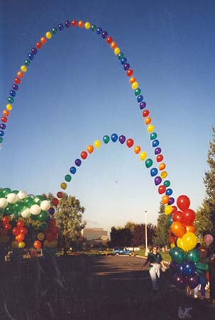 two 50 foot tall single balloon style arches created with balloons in alternating sequences of rainbow colors (green, red, yellow, blue, inigio, and violet) for an outdoor event. Single balloon arches are also known as Sting of Pearls style arches.