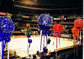 Red and blue 30 inch balloons floating on 8' ribbons serving as area decoration in the arena seating area