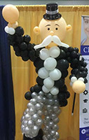 This six-foot high balloon sculpture of a classic Wall Street bank character wears a ballon tuxedo with top hat, and displays a large handlebar moustache