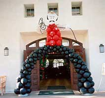 20 foot tall balloon sculpture of a cowboy with lasoo and bowed legs framing the entrance to a wild west theme party