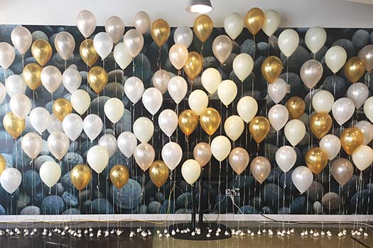 A linear arrangement of gold, white and silver helium-filled balloons forming a tapestry wall decoration.