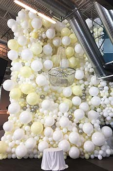 This 30 foot tall wall of white and cream latex balloons was constructed to serve as a visual border - backdrop for a winter holiday party in a venue with very high ceilings
