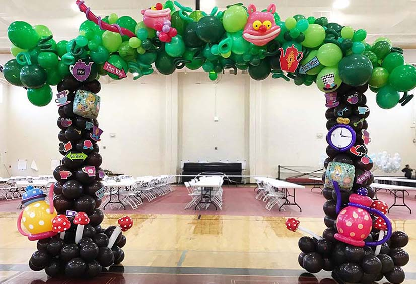 An eight six foot tall entrance decoration for an Alice In Wonderland theme event adorned with theme items lie the Cheshire Cat, teapots, a watch, and so forth