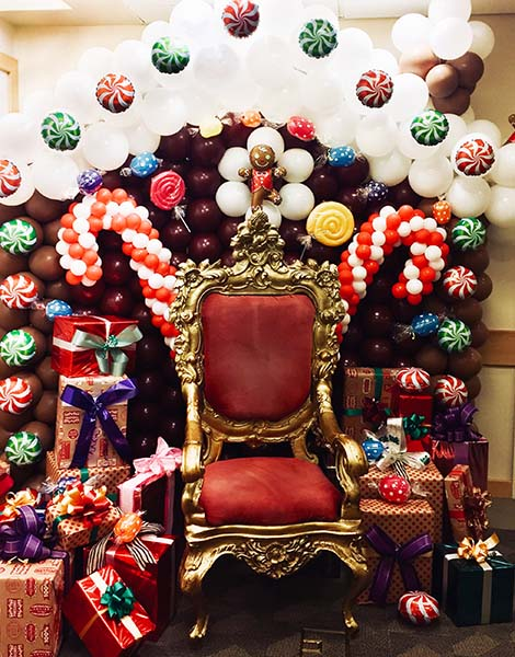A Five Foot Tall Santa Chair Surrounded By Christmas Decorations