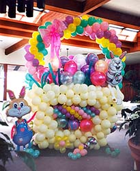 An eight foot tall easter basket sculpted out of lates balloons in pastel colors serves as a focal decoration at an Easter  brunch event.