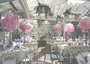 36 inch crystal bubble balloons partially filled with smaller pink balloons serve as a centerpieces for a Mother's Day event.