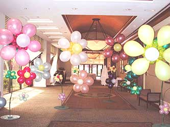 A hall filled with six foot tall ballon fantasy flowers give a garden-like appearance