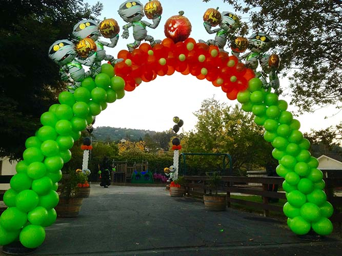 This lime green and orange swirled-style balloon arch is topped by floating Halloween critters serving as the entrance decoration for a Halloween event
