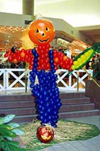 A six foot tall balloon sculptire of a scarecrow complete with coveralls and an ear of corn.