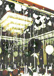 The ceiling above this dance floor is filled with floating black and white balloons each suspending a mylar streamer.
