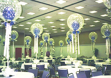 The tables in this room are decorated with clear 30 inch magical bubble balloon centerpieces adorned with white stars with a blue balloon inside each bubble.