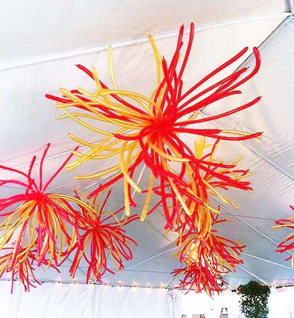 These clusters of approximately 30 slender 3 foot long red and gold long balloons each spray outward from the ceiling of a tent giving it a surreal and modern appearance.