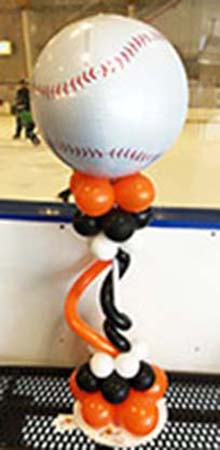 This Balloonatics baseball-themed centrpiece has a giant baseball balloon on top of a stqnd decorated in twisting balloons in team colors.