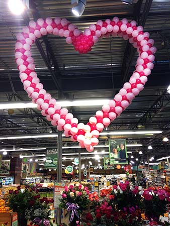 This 10 foot tall Valentine Heart sculpture is suspended from the ceiling of a Whole Foods market as a Valentine decoration.