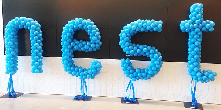 A 4 foot tall balloon logo sculpture of the NEST logo created as four individual air-filled letters for an event at NEST headquarters