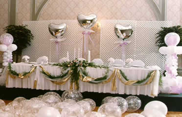 Floating silver Mylar® hearts and flanking columns center attention on the wedding party at the head table & Wedding and Wedding Reception balloon and fabric decorations